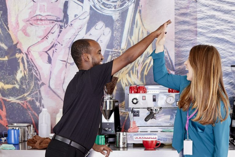 A black male and a white female high five each other in front of a coffee machine, smiling at each other