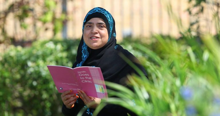 A lady in a headscarf sitting in the Bromley by Bow garden reading an ESOL booklet