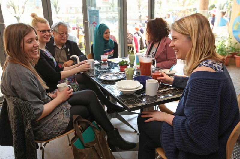 A group of 6 smiling people chatting with drinks in the Bromley by Bow Centre cafe