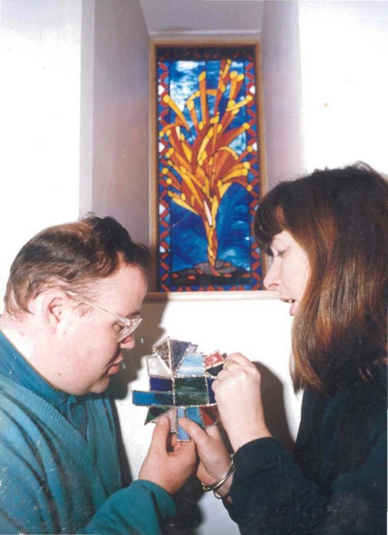 Two people looking at a piece of stained glass window artwork
