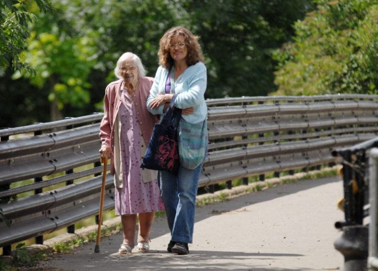 A younger lady helping an older lady with a walking stick