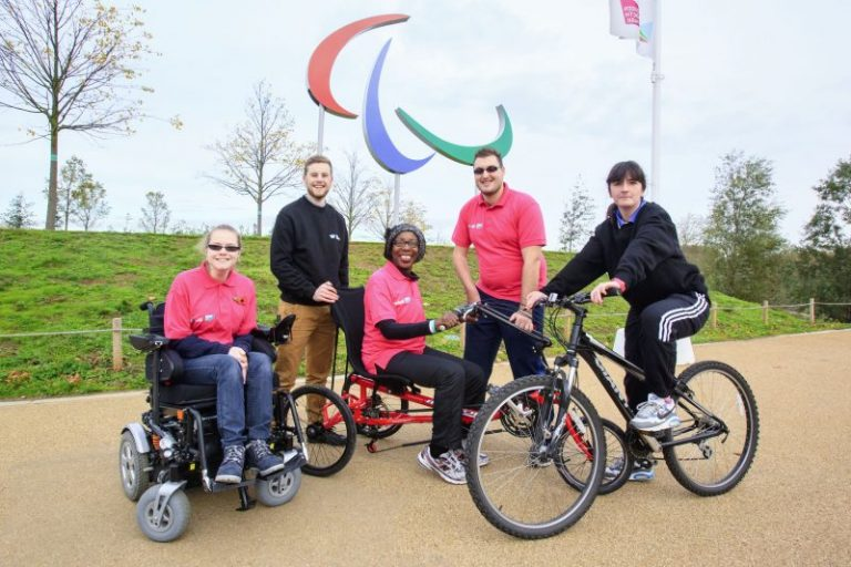 A group of 6 people in black and pink clothing smiling at the camera in the London Olympic Park, in front of the paralympic logo. One is in a wheelchair, one on a bike and one using a bike adapted for people with disabilities