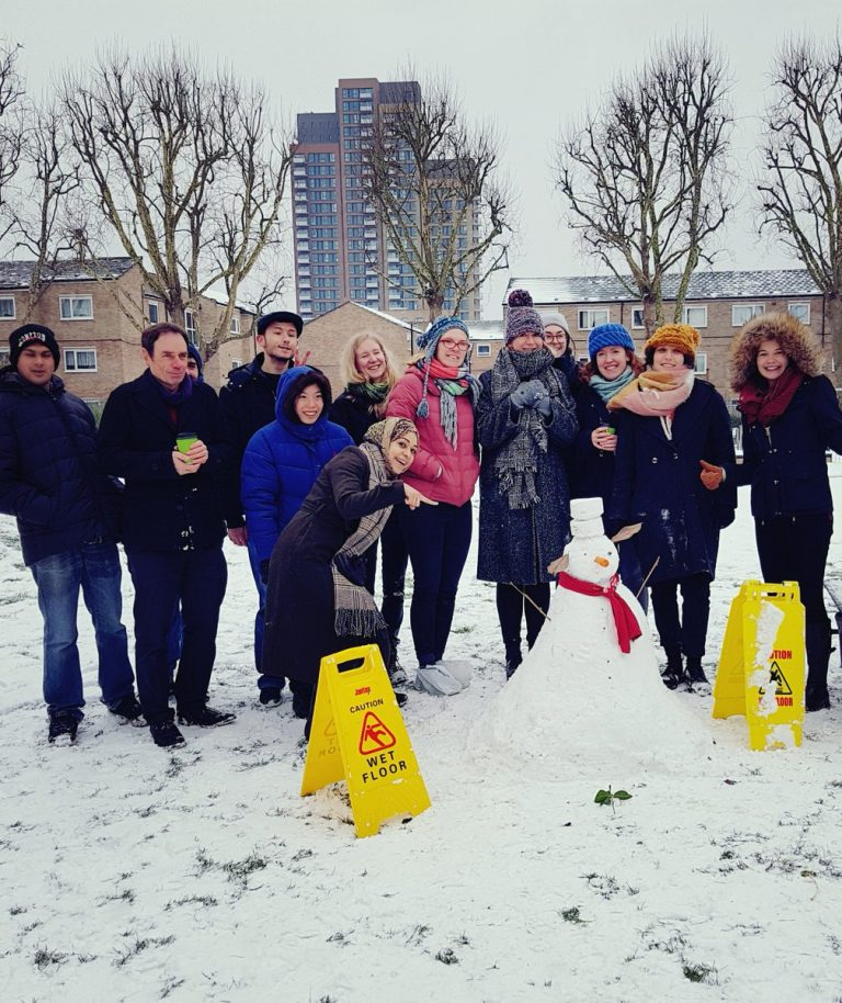 A group of staff in woolly hats and coats smile at the camera in the snowy park at the Bromley by Bow Centre, behind a snow man