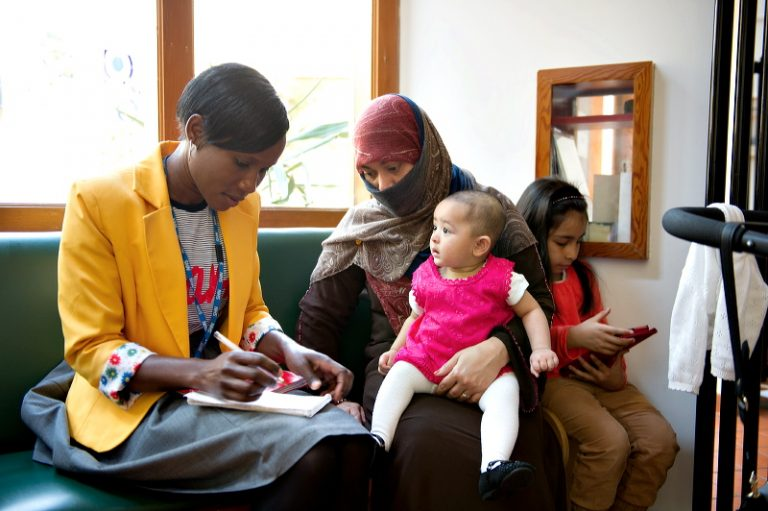 A black lady in a yellow jacket speaks with a lady in a head scarf holding a baby in pink on her lap in the Bromley by Bow Health Centre waiting room