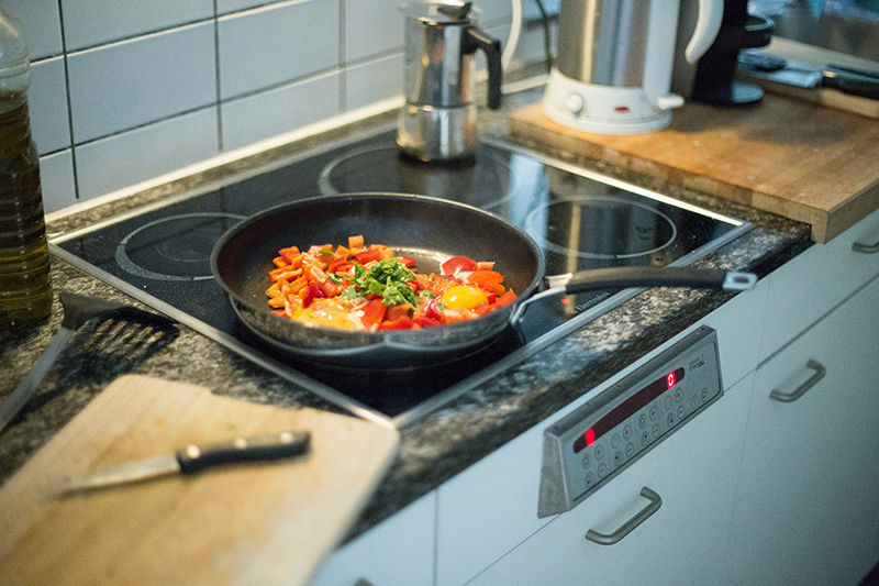 Pan of food cooking on hob in a kitchen with kettle in the background