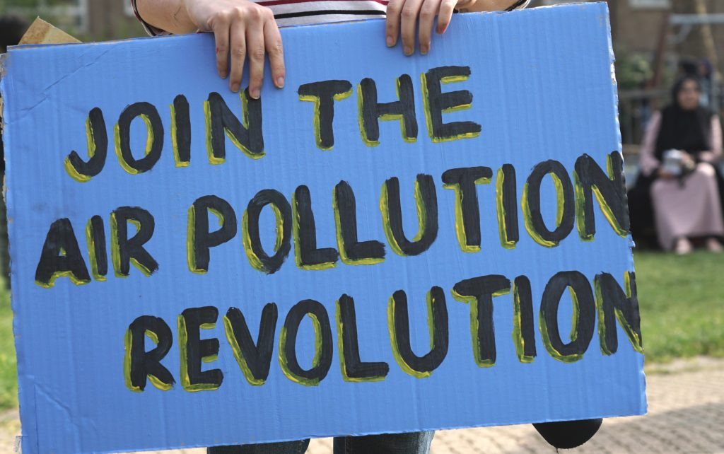 Blue and black painted banner saying 'Join the air pollution revolution'
